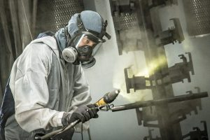 Man coating a metal rack