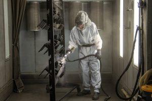 Man powder coating in a hazmat suit