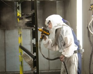 Closeup of a man powder coating in a white hazmat suit